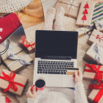 Handmade Gifts Cover Photo. Woman Sitting on pile of gifts on laptop holding credit debt card and black coffee