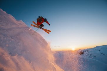 Person Skiing Off Mountain With Jump Trick