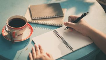 Writing On Table In Open Blank Notebook With Coffee And Two Closed Notebooks