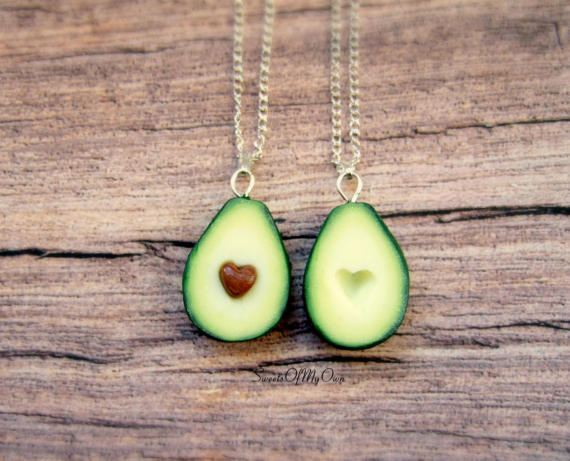 Avocado earnings on wooden background with golden chain